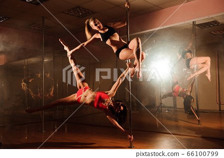 Pole fitness instructor helping a student do a 66100799