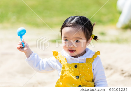 Kids and family playing with sand in park 66101285
