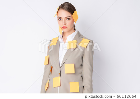 Business woman wears light brown suit standing on white background with a lot of post it on her body 66112664
