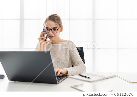 Beautiful woman is working at home with her laptop. The woman is talking on the mobile phone 66112670