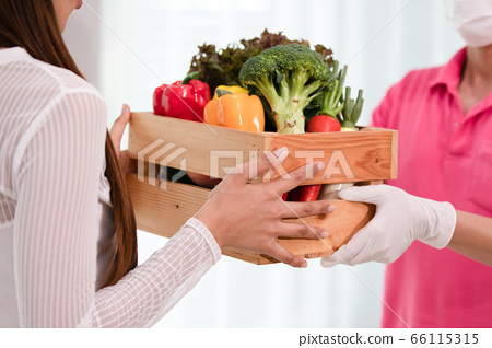 Delivery man sending wooden box of fresh organic fruits and vegetable 66115315