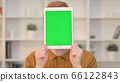Portrait of Man holding Tablet with Chroma Screen over his Face  66122843
