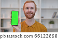 Portrait of Redhead Man showing Smartphone with Chroma Screen  66122898