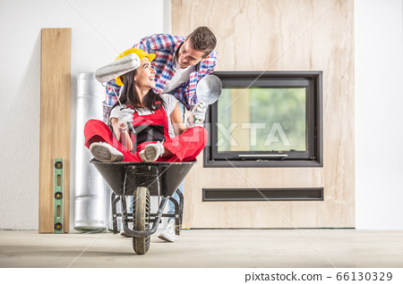 Happy couple having fun riding a wheelbarrow 66130329