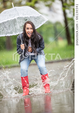Happy girl jumping in puddles in rainboots, 66130341