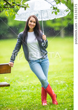 Smiling good looking woman leans against a park 66130375