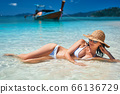 Summer dreams. Beautiful sexy woman in white bikini and straw hat relax in turquoise sea water on tropical beach in paradise island 66136729