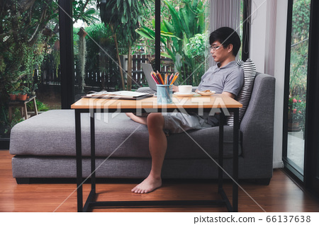 A man in casual wear uusing laptop while he is working. 66137638
