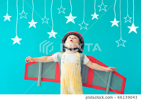 Happy child playing with toy paper wings against 66139043