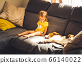 Baby with dog on sofa in bright room. 66140022
