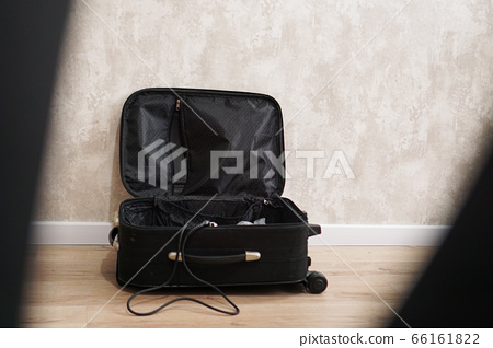 Opened empty black suitcase for different things on gray background 66161822