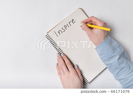 INSPIRE inscription. Female writing in Notepad. 66171076