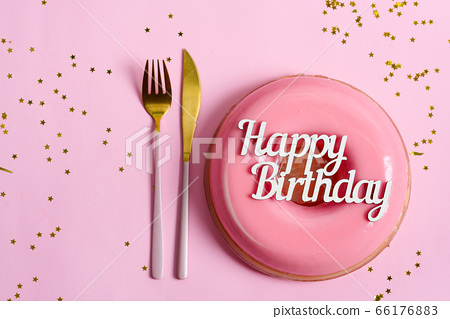 Text Happy Birthday above freshly cooked homemade fruit glazed dessert on a pink background with fork and decoration. 66176883