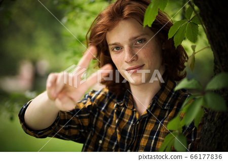 Victory gesture from Red-haired freckled guy posing in nature. Selective focus on young charming man in checkered shirt showing V or Victory sign which means a symbol of peace 66177836