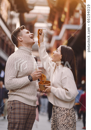 newlywed couple eating noodles with chopsticks in Shanghai outside a food market 66194019