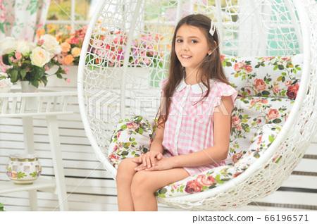 Portrait of happy little girl posing on swing 66196571