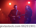 A jazz singer and guitarist perform on stage. 66201901