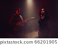 A jazz singer and guitarist perform on stage. 66201905