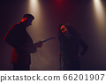A jazz singer and guitarist perform on stage. 66201907