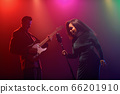 A jazz singer and guitarist perform on stage. 66201910