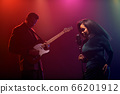 A jazz singer and guitarist perform on stage. 66201912