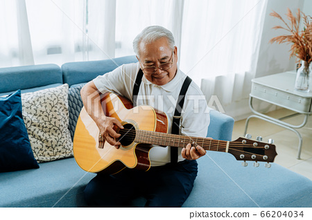 Asian senior man sitting on the sofa and playing acoustic guitar. Happy smiling elderly singing and enjoying with guitar. Enjoying retirement life at home. 66204034