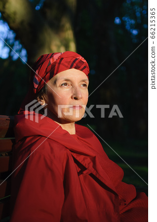 Elderly tired woman in red clothes in park sitting on the bench and enjoying a good weather and sunset in the park during a spring or autumn 66215365