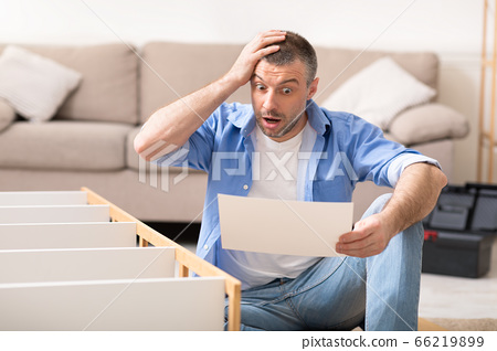 Shocked Man Assembling Furniture Scratching Head Reading Inctruction Sitting Indoor 66219899