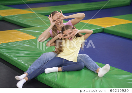 Cute child with mom fooling around at trampoline park 66219980