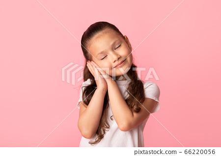Lovely little asian girl with happy serene face pretending to sleep 66220056