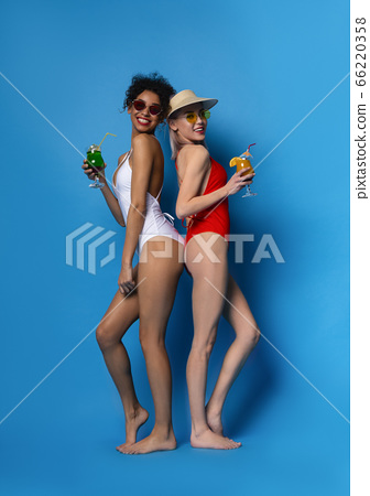 Beautiful Young Girls In Swimsuits Holding Summer Cocktails And Smiling At Camera 66220358