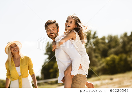 Happy Family Enjoying Summer Day Together, Father Carrying Daughter Outdoors 66220542