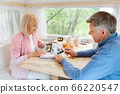 Senior married couple looking through family album with photos inside of camping vehicle 66220547
