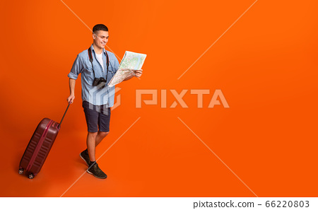 Male traveler with suitcase holding map, going towards copy space 66220803