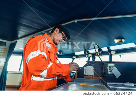 Filipino deck Officer on bridge of vessel or ship. He is plotting position on chart 66224424