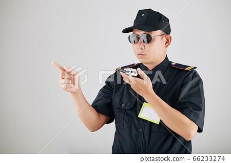 Policeman using police radio 66233274
