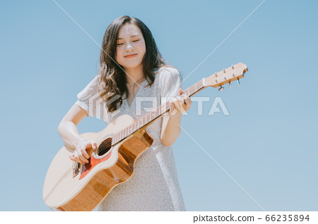 Beautiful woman playing guitar on blue sky background 66235894