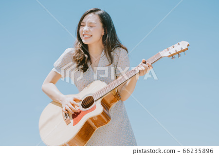 Beautiful woman playing guitar on blue sky background 66235896