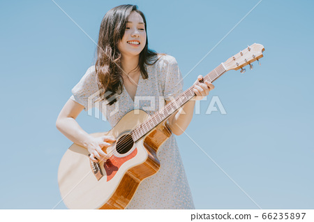 Beautiful woman playing guitar on blue sky background 66235897
