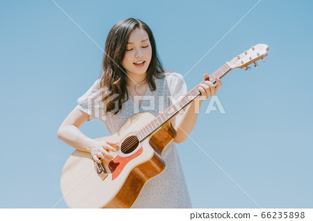Beautiful woman playing guitar on blue sky background 66235898