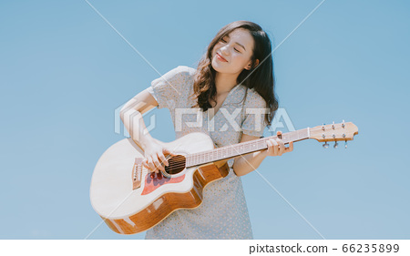 Beautiful woman playing guitar on blue sky background 66235899
