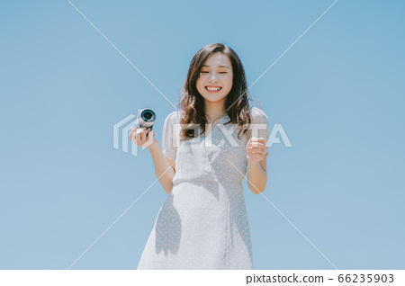 Beautiful woman holding a camera on blue sky background 66235903