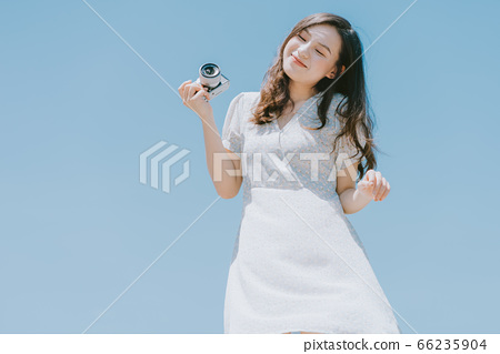 Beautiful woman holding a camera on blue sky background 66235904