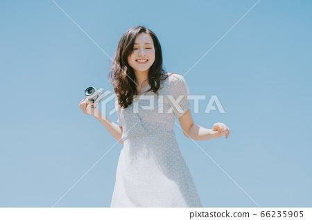 Beautiful woman holding a camera on blue sky background 66235905