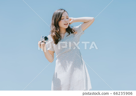 Beautiful woman holding a camera on blue sky background 66235906