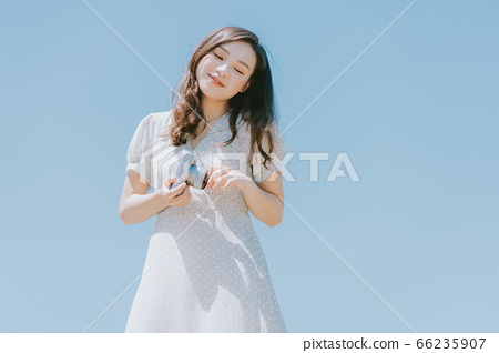 Beautiful woman holding a camera on blue sky background 66235907