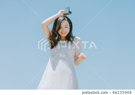 Beautiful woman holding a camera on blue sky background 66235909