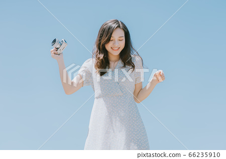 Beautiful woman holding a camera on blue sky background 66235910