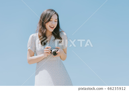 Beautiful woman holding a camera on blue sky background 66235912