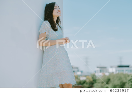 A beautiful woman lean on the wall and holding a camera 66235917